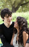 Teen couple sitting on bench outdoors smiling Royalty Free Stock Images