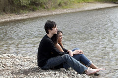 Teen couple sitting on stony river bank Stock Photos