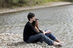 Teen couple sitting on stony river bank Stock Photos