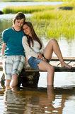 Teen couple sitting on water pier Royalty Free Stock Photos