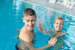 Teen couple splashing at the pool Royalty Free Stock Image