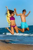 Teen couple in swim wear jumping. Royalty Free Stock Photography