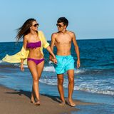 Teen couple in swim wear walking along beach. Stock Photos
