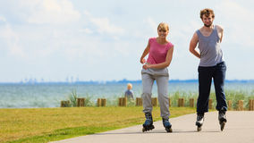 Teen couple together on skates. Royalty Free Stock Image