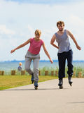 Teen couple together on skates. Royalty Free Stock Photo