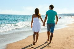 Teen couple walking away on beach. Royalty Free Stock Images
