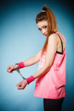 Teen crime - teenager girl in handcuffs. Teen crime, arrest and jail - Criminal teenager girl prisoner woman in handcuffs blue background stock photo