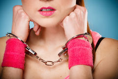 Teen crime - teenager girl in handcuffs. Teen crime, arrest and jail - Criminal teenager girl prisoner woman in handcuffs blue background royalty free stock image