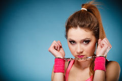 Teen crime - teenager girl in handcuffs. Teen crime, arrest and jail - Criminal teenager girl prisoner woman in handcuffs blue background stock photography