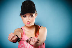 Teen crime - teenager girl in handcuffs. Teen crime, arrest and jail - Criminal teenager girl prisoner woman in handcuffs blue background royalty free stock photos