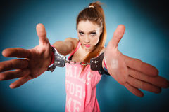 Teen crime - teenager girl in handcuffs. Teen crime, arrest and jail - Criminal teenager girl prisoner woman in handcuffs blue background royalty free stock photo