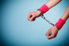 Teen crime - teenager girl in handcuffs. Teen crime, arrest and jail - Hands of criminal teenager girl prisoner woman in handcuffs blue background stock photos
