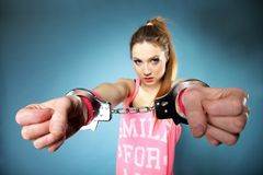 Teen crime - teenager girl in handcuffs. Studio shot blue background stock photos