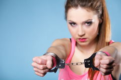 Teen crime - teenager girl in handcuffs. Studio shot blue background stock photo