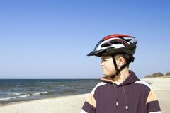 Teen with cycle helmet by sea. Side portrait of young boy with protective bicycle helmet on sandy beach; sea in background Stock Photo