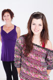 Teen daughter. Portrait in studio, background is her middle aged mother Royalty Free Stock Photos