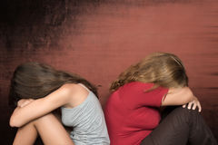 Teen daughter and mother sitting on the floor crying stock photos