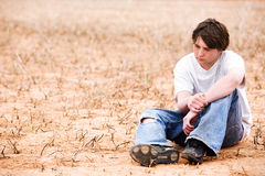 Teen depression. Teenager sitting depressed in dry lakebed amongst the weeds, contemplating stock images