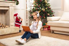 Teen with digital tablet at christmastime. Happy teenage girl in headphones using digital tablet at home at christmastime stock photo