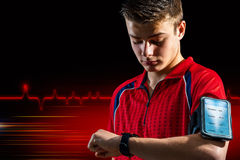 Teen doing fitness analysis on smart watch. Conceptual portrait of teen sports man reviewing personal records on smart watch. Boy wearing armband with smart Royalty Free Stock Images