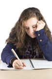Teen doing her homework. A teenage girl doing her homework at a table Royalty Free Stock Photos