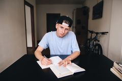 The teen is doing homework while sitting in his room. A look at the camera. Royalty Free Stock Photo