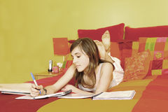 Teen doing lessons. Young girl doing lessons laying in a bed royalty free stock photos