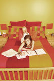 Teen doing lessons. Young girl laying in a bed doing lessons stock image