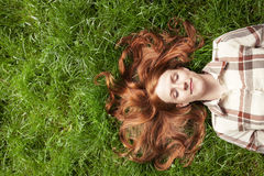 Teen dreaming in grass with eyes closed Royalty Free Stock Photography