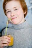 Teen dricka fruktsaft för Redhead Arkivfoto