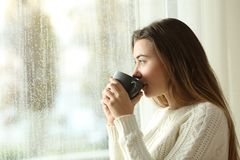 Teen drinking coffee looking through a window a rainy day. Side view portrait of a relaxed teen drinking coffee looking outside through a window in a rainy day Stock Images