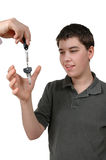Teen Driver. Young Teenage boy reaches for the keys to the car. He is new to driving Stock Photography