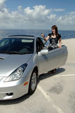 Teen driver with new car. A happy young woman standing next to her car parked at the beach holding out her keys stock photography
