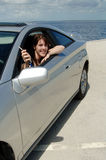 Teen driver with new car. A happy young woman in her car parked at the beach holding out her keys royalty free stock images