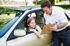 Teen Driver Passed Test. Teen girl reviews her score on the driving test with the instructor Royalty Free Stock Photos