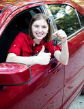 Teen Driver - Thumbs Up. Teenage girl in the car driver's seat, holding keys and giving a thumbs up sign Stock Image