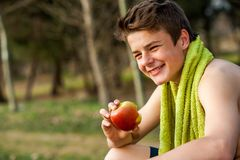 Teen eating apple after ecercise. Teen jogger eating apple after exercise outdoors Stock Photos