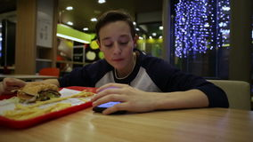 Teen Eating French Fries and Using Smartphone. Teenager Eating French Fries and Using Smartphone stock video footage