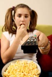 Teen eating popcorn. Teenager having remote in hand and eating popcorn during a movie Stock Photos