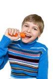 Teen eats carrots. Royalty Free Stock Photography