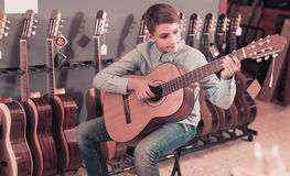 Teen examining  acoustic guitars Royalty Free Stock Photography