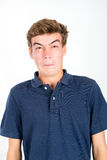 Teen faces. Disgusted teenage boy making faces isolated in white Royalty Free Stock Photos