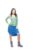 Teen fashion. Young teen in the shirt blue petticoat and winter boots on a white background Royalty Free Stock Photography