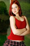 Teen fashion. Red haired seventeen year old cutie wearing red tank top with skirt Stock Image