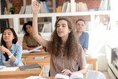 Teen female college university student raising hand during class royalty free stock photo