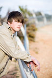 Teen on fence portrait. Teen portrait outdoors leaning on a fence stock photo
