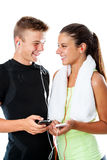 Teen fitness couple with smart phones. Royalty Free Stock Image