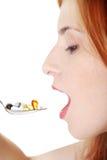 Teen flicka som tar pills från skeden. Fotografering för Bildbyråer