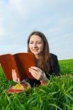 Teen flicka som utomhus läser bibeln Arkivbild