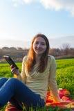 Teen flicka som utomhus läser den elektroniska boken Arkivfoton